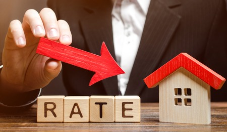 Businessman holding the down arrow on wooden blocks with the word Rate and house. Low interest in mortgages. Reducing interest payments for mortgage. The fall in housing rates on credit. Stock Photo