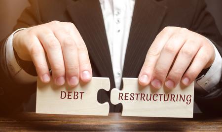 Geschäftsmann sammelt Holzklötze mit dem Wort Umschuldung. Schuldenerlass. Kreditrückzahlungsbedingungen ändern. Ändern des Zeitpunkts und der Höhe der Zahlung. Umtausch von Schulden gegen einen Anteil an der Immobilie