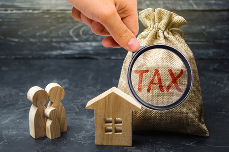 A bag with the word Tax and family stand near the house. Taxes on real estate, payment. Penalty, arrears. Register of taxpayers for property. Law-abiding, evasion of payment. Court law. Luxury tax.