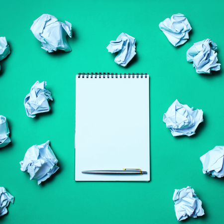 white notebook with pen on a green background among paper balls. The concept of generating ideas, inventing new ideas. Paper balls are all around. Searching of decisions. Bad idea. Business Banque d'images