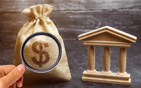 Eine Tasche mit Dollargeld und eine Bank oder ein Regierungsgebäude. Einlagen, Investitionen in das Budget. Zuschüsse und Subventionen. Zahlung von Steuern. Zentralbank. Kredittranchen und Leasing. Schuldenrückzahlung.
