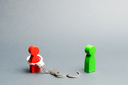 A man is bound by handcuffs standing near a free person. Exemption from debt or physical slavery. Parting or divorce of two persons. The end of the relationship. Exemption from obligations.