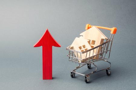Holzhäuser in einem Einkaufswagen und roter Pfeil nach oben. Das Konzept der Erhöhung der Wohnkosten. Hohe Nachfrage nach Immobilien. Das Wachstum von Mieten und Hypothekenzinsen. Verkauf von Wohnungen Standard-Bild