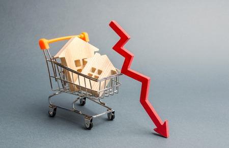 Miniaturowe drewniane domy i czerwona strzałka w dół. Pojęcie nieruchomości o niskich kosztach. Niższe oprocentowanie kredytów hipotecznych. Spadające ceny wynajmu mieszkań i mieszkań. Zmniejszenie popytu na zakup domu