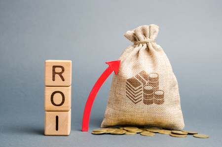 Wooden blocks with the word ROI and the up arrow with the money bag. High level of business profitability. Return on investment, invested capital, rate. Success. Growth. Profitability. Analytics.