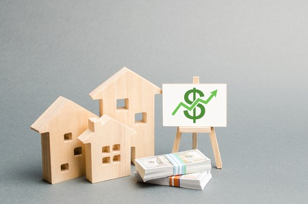 Wooden figures of houses and a poster with money. The concept of real estate value growth. Increase liquidity and attractiveness of assets. Raising the rent or cost of buying a home.