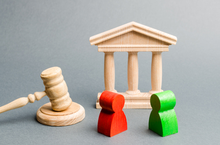 Wooden figures of people standing near the judge's gavel. Litigation. Business rivals. Conflict of interest. Law and justice. The layer's services. Two opponents. Judgment. Gavel. Red and green