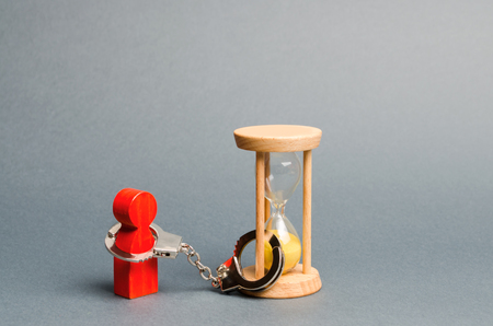 Severely ill person who has little time left. Time limit. Adulthood. Isolation from society in prison. Probation. Dependence, management on time. Hourglass and handcuffs. Suspended sentence