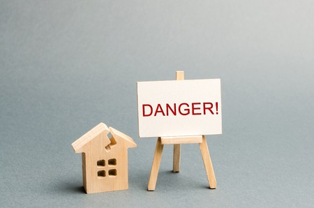 Shabby housing. Inscription Danger. The concept of an emergency house. Old house from which evacuation of residents is required. Building demolished. Renovation and renovation of historic buildings.