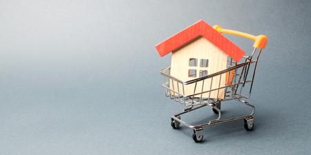 Holzhaus in einem Supermarktwagen. Das Konzept des Kaufs eines Hauses oder einer Wohnung. Bezahlbares Wohnen. Profitable und günstige Kredite für Immobilien. Ein Haus kaufen. Hypothek und Darlehen. Platz für Text