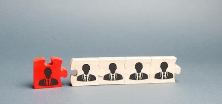 Holzpuzzles mit dem Bild von Arbeitern. Das Konzept des Personalmanagements im Unternehmen. Entlassung eines Mitarbeiters aus einem Team. Degradierung. Schlechter Arbeiter. Personalkürzungen. Humanressourcen. Degradieren