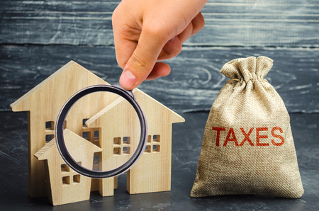 Bag with the money and the word Taxes and wooden houses. Taxes on real estate, payment. Penalty, arrears. Register of taxpayers for property. Law-abiding, evasion of payment. Court law. Luxury tax. Banque d'images - 122679708