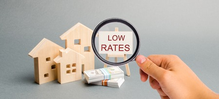 Een vergrootglas kijkt naar een poster met het woord lage tarieven en houten huis. Het concept van het verlagen van de rente op hypotheken. Huisvesting op krediet. Huurt. Kapitalisatie van onroerend goed. Verzekering