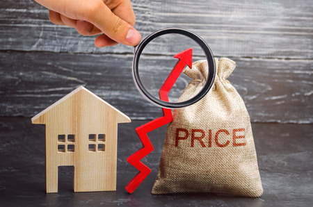 Bag with the money and the word Price and up arrow and wooden house. The increase in housing prices. Rising in fees for an apartment. The rise in property prices. The growth of utilities 免版税图像