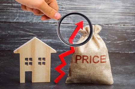 Torba z pieniędzmi i napisem Cena i strzałka w górę i drewniany dom. Wzrost cen mieszkań. Podwyżka opłat za mieszkanie. Wzrost cen nieruchomości. Rozwój mediów