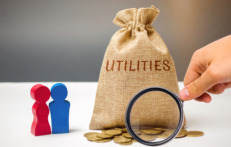A money bag with the word Utilities and a family. The concept of saving money for the payment of utilities. The accumulation of money. A large debt. Electricity bill, heating. Debt repayment Stok Fotoğraf