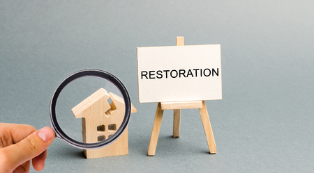 A poster with the inscription Restoration and a broken wooden house. Repair secondary housing. The process of improvement, reconstruction of the home. Recovery after a fire or natural disaster