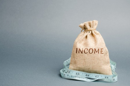 Money bag with the word Income and measuring tape. Reduced revenue and profits. Reduced budget. Loss of money. Unsuccessful business and poverty. Lower salary, wage rates. Financial crisis