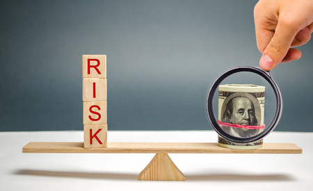 Dollars and the inscription Risk on the scales. The concept of financial risk and investing in a business project. Making the right decision. Property insurance. Legal and market risks