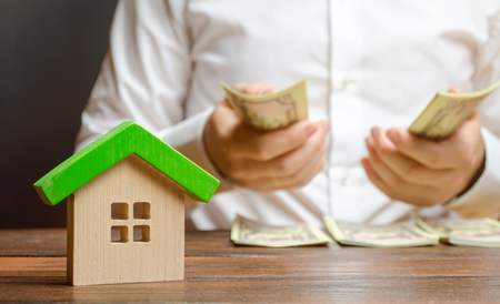 A man counts money on the background of the figures of the house. Calculation of property tax, payment of utilities. Counting repairing costs or buying a home. Financial difficulties, micromanagement