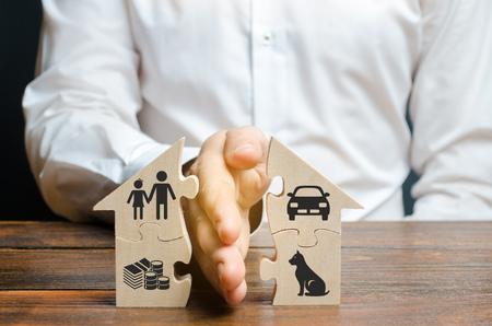 Een man deelt een huis met zijn handpalm met afbeeldingen van eigendommen, kinderen en huisdieren. Echtscheidingsconcept, proces van eigendomsverdeling. Huwelijkscontract, voogdij over kinderen. De diensten van de laag Stockfoto