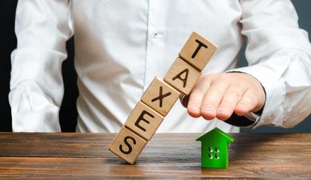 Un homme protège sa main avec une figurine d'une maison d'une tour de cubes qui tombe avec le mot impôts. Charge fiscale élevée, protection des intérêts des petites et moyennes entreprises, compétitivité.