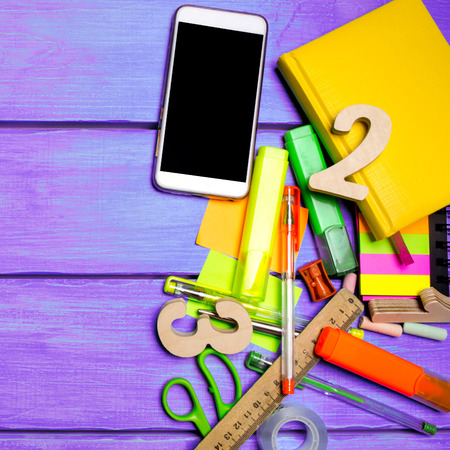 school supplies in the school desk, stationery, school concept, blue background, creative chaos, space for text, markers, pens, notepads, stickers. copyspace Banco de Imagens