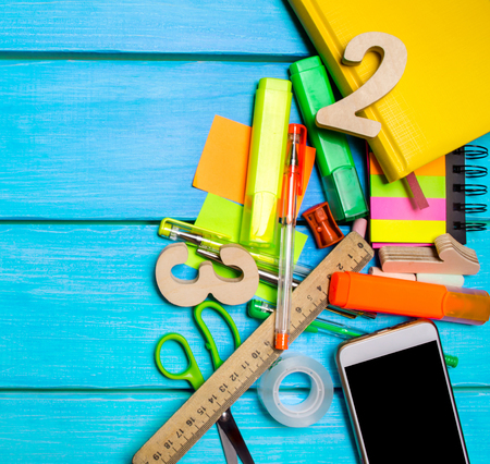 school supplies in the school desk, stationery, school concept, blue background, creative chaos, space for text, markers, pens, notepads, stickers. copyspace. top view. flat lay