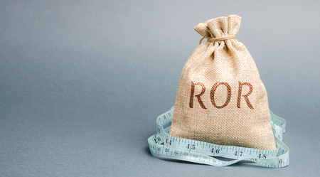 Money bag with measuring tape and the word ROR. Financial ratio illustrating the level of business loss. Return on investment. Recession. Lower profitability and performance Stock Photo