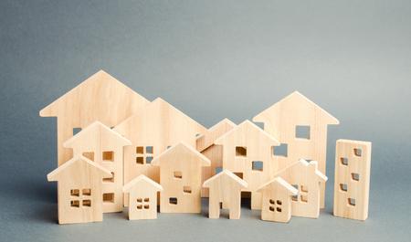 Miniatur-Holzhäuser. Immobilien. Stadt. Agglomeration und Urbanisierung. Analyse des Immobilienmarktes. Nachfrage nach Wohnraum. Steigende und fallende Immobilienpreise. Das Wachstum der Stadt und ihrer Bevölkerung Standard-Bild