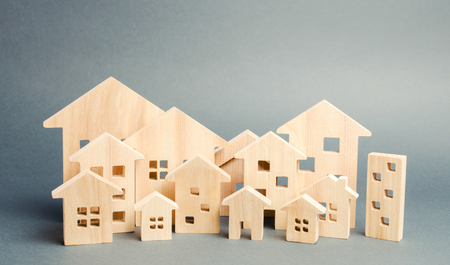 Miniature wooden houses. Real estate. City. Agglomeration and urbanization. Real Estate Market Analytics. Demand for housing. Rising and falling home prices. The growth of the city and its population Banque d'images - 124956033