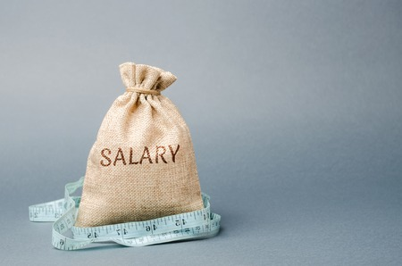 Money bag with the word Salary and tape measure. Wage cuts. The concept of limited profit. Lack of money and poverty. Small income. Salary reduction. Unsuccessful business. Financial crisis Stock Photo