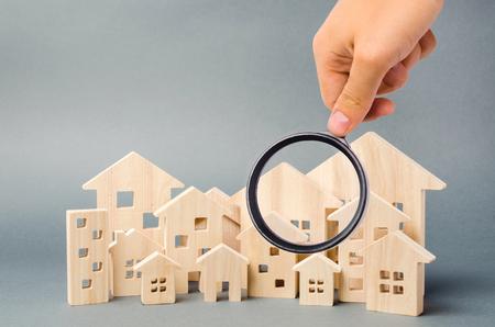 Holzhäuser und Lupe. Immobilienbewertung. Hausbewertung. Standortwahl für den Bau. Haussuchkonzept. Suche nach Wohnungen und Wohnungen. Immobilien