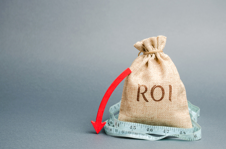 Money bag with measuring tape and the word ROI. Financial ratio illustrating the level of business loss. Return on investment. Recession. Lower profitability and performance. Arrow to down