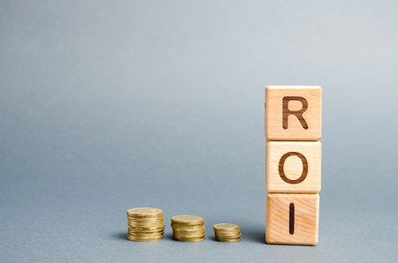 Wooden blocks with the word ROI and coins. High level of business profitability. Return on investment, invested capital, rate. Success. Growth. Profitability. Analytics. Stock Photo