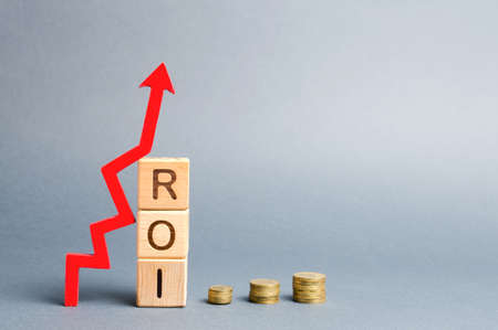 Wooden blocks with the word ROI and arrow up. High level of business profitability. Return on investment, invested capital, rate. Success. Growth. Profitability. Analytics. Report Stock Photo