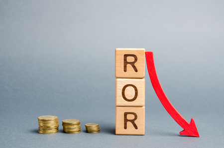 Wooden blocks with the word ROR and arrow down. Financial ratio illustrating the level of business loss. Return on investment. Recession. Lower profitability and performance Stock Photo