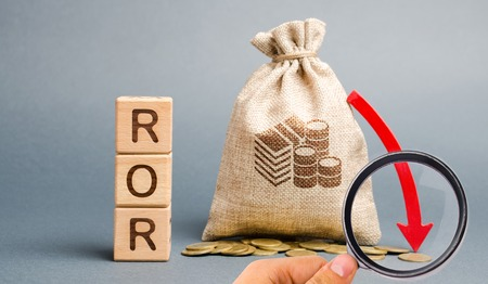 Wooden blocks with the word ROR, money bag and down arrow. Financial ratio illustrating the level of business loss. Return on investment. Recession. Lower profitability and performance