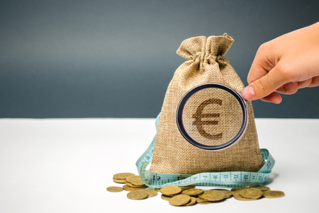 Money bag with a euro sign and tape measure. Limited budget. Lack of money. The concept of accumulating money in the family budget. Family Insurance. Distribution of cash savings. Saving money