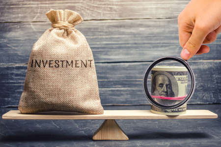 Money bag with the word Investments and dollars on scales. Attraction of financial resources for investment projects. Risk assessment and profit forecast. Investment portfolio. Payback