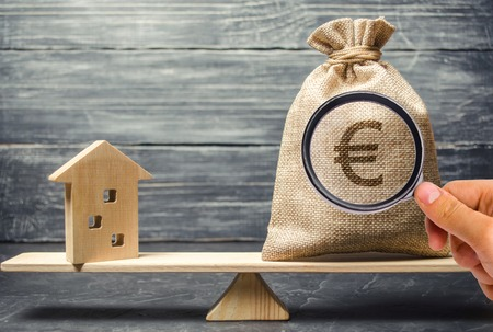 A money bag and a wooden house on the scales. The concept of real estate purchase. Sale of property. Payment of the mortgage. Redemption of taxes. Tax refund. Legacy  Inheritance tax concept