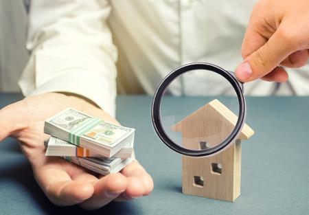 L'homme d'affaires détient des dollars en mains près d'une maison en bois. Concept d'investissement immobilier. Hypothèque. Prêt pour le logement. Crédit. Louer. De location. Acheter une propriété. L'accumulation d'argent. Vendre une maison Banque d'images