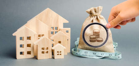 Bag with money and tape measure with a wooden houses. The concept of a limited real estate budget. Low subsidies. Lack of investment in construction. Market crisis. Bankruptcy
