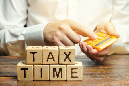 Wooden blocks with the word Tax time and taxpayer with a calculator. The concept of paying the tax rate. Taxation  burden. Pay off debts. Property  income annual taxes.