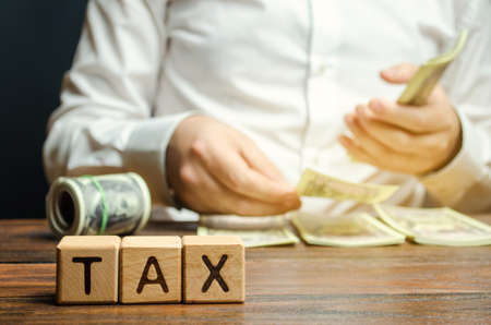 Wooden blocks with the word Tax and a businessman who counts money. The concept of time payment of taxes. Tax rates. Taxation  burden. Pay off debts. Property taxes