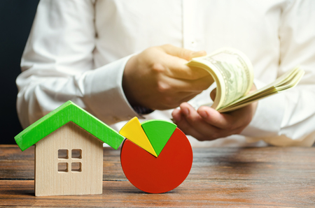 A miniature wooden house and a pie chart. Businessman counts money. Concept of real estate market analysis and analytics. Segmentation and marketing. Budget and maintenance costs of the buildings.