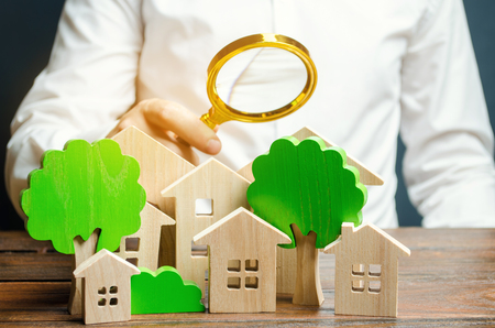 A man holds a magnifying glass over wooden houses and trees. Real estate valuation and selection of a place for the construction of new buildings. Evaluation of urbanism and residential space. Stock Photo