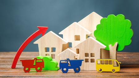 Wooden houses, vehicles, trees and up arrow. The concept of increasing air pollution. The growth of traffic in the city. Favorable business climate. Increase the construction of new buildings.