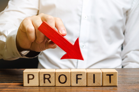 Businessman holds down arrow over word Profit. The concept of low profits in the company. Unprofitable business. Financial crisis. Capital outflow. Bankruptcy. Financial market fall