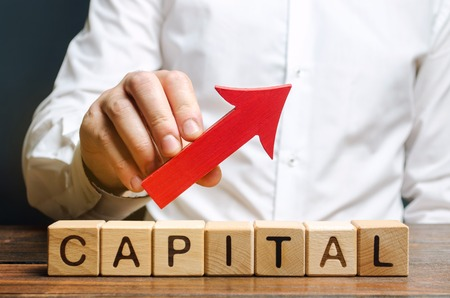 Man holds red arrow up above word Capital. Increase investment and foreign capital in the national economy. Improve business climate and increase attractiveness. Growth and stability of the economy Banco de Imagens
